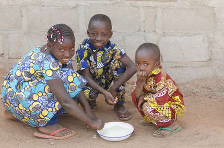 Three African Children Sitting Outdoors Eating Rice in Africa Zdjęcie Seryjne - 103509391