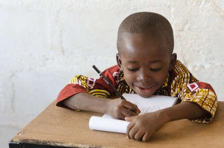 Afrikanischer schwarzer Junge bei der Schule , die mit Kopienraum schreibt
