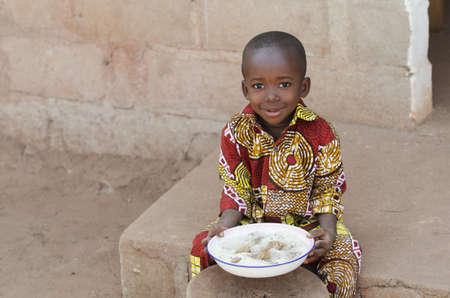 屋外でご飯を食べる小さな黒人アフリカの少年の率直なショット