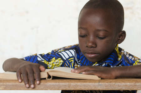 Little African Boy Reading Big Book at School with copy space