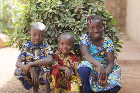 Three gorgeous African children posing outdoors Smiling and Laughing