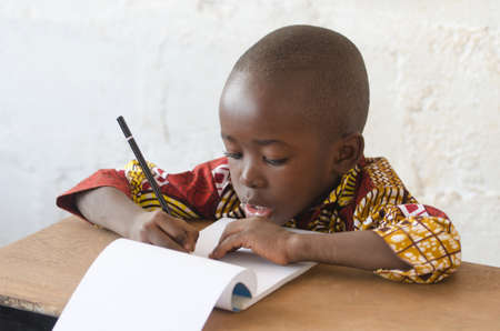 Handsome Young African Boy Writing and Learning in School Building