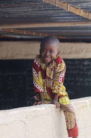 Adorable African Child Sitting on Wall at School
