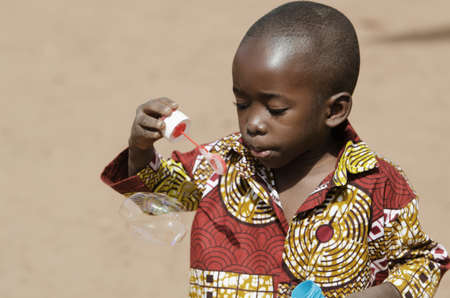 Handsome African baby boy having fun outdoors with soap bubbles