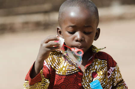 African black boy Blowing Bubbles Outdoors