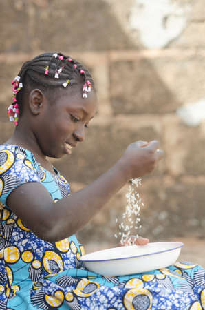 Adorable Portrait of Little African Girl Preparing Rice for Meal Zdjęcie Seryjne - 95246846