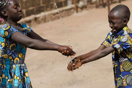 Two African Children Cleaning Hands Outdoors with Fresh Water