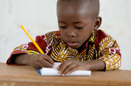 Little African Black Baby Boy in the Classroom Writing Notes