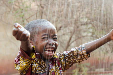 Little Native African Boy Standing Outdoors Under the Rain Imagens