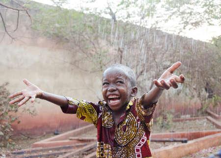 Sweet little African boy under the rain in Mali (Africa) 스톡 콘텐츠