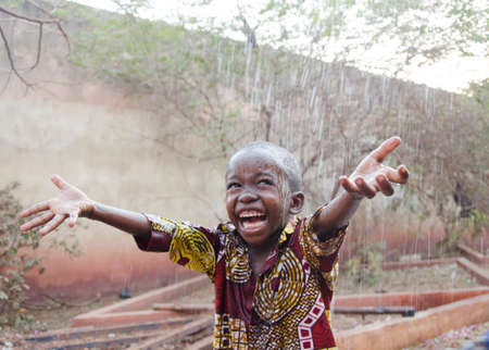 Sweet little African boy under the rain in Mali (Africa) Standard-Bild