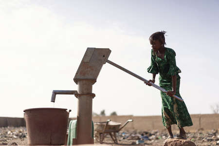 Young West Africa Woman Carrying Natural Water in a village 写真素材