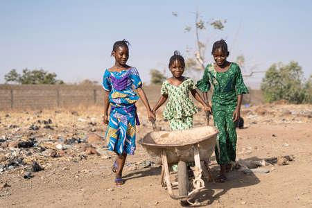 Écolière noire authentique transportant de l'eau pure dans un village