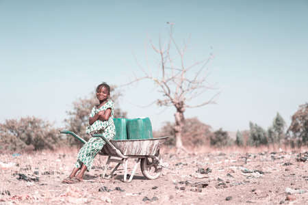 Cute West Africa Woman Transporting Clean Water with major difficulties