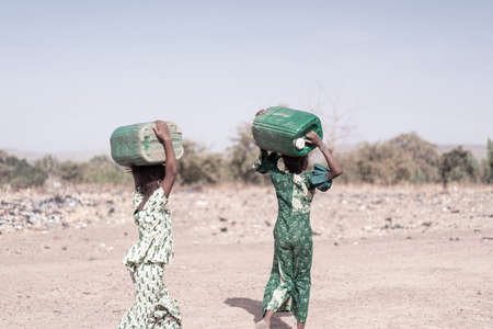 Tiny Native African Young Woman Gathering Pure Water in a typical village