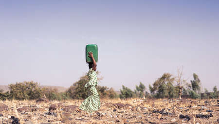 Candid photo of African Girl Saving fresh Water in an arid zone