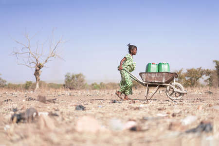 Pequeña mujer africana transportando agua dulce como símbolo de la sequía