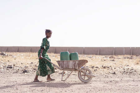 Authentic Native African Girl Carrying Fresh Water for lack of water symbol