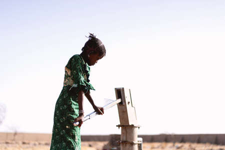 Little Black Women Carrying Pure Water with major difficulties Imagens