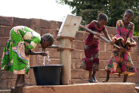 African Children At A Public Borehole Fetching Water For Their Families Stock Photo