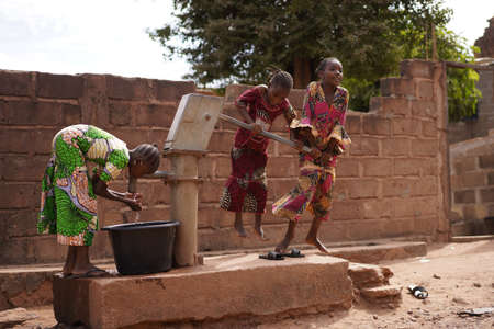 Three African Girls Showing Off Teamwork Skills Collecting Water At a Borhole Hand Pump