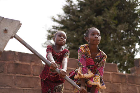 Two African Girls Having a Hard Time Pumping Water From The Public Well