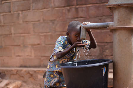 Little African Boy At The Community Borehole Quenching His Thirst