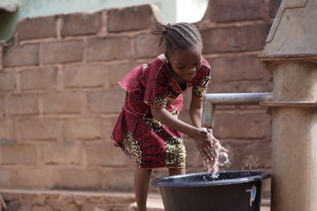 Small African Girl Washing Her Hands At The Village Well Archivio Fotografico