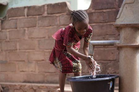 Kleines afrikanisches Mädchen, das sich am Dorfbrunnen die Hände wäscht Standard-Bild
