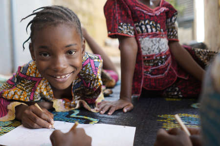 Close up Portrait of Black African Schoogirl Smiling and drawing on paper