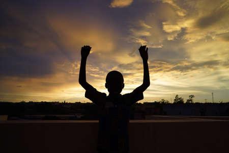 Hübscher afrikanischer Junge winkt vor der Abendsonne