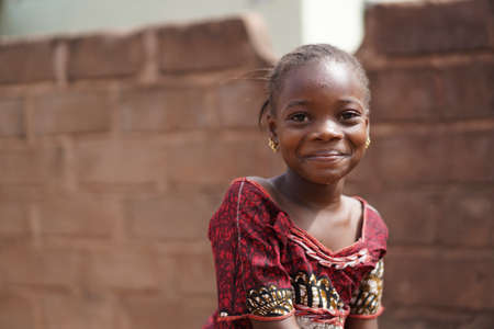 Smiling African Girl With a Wet Face After Having Taken A Sip From The Water Borehole Stockfoto