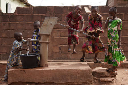 African Children Having Fun While Taking Water From A Hand Pump