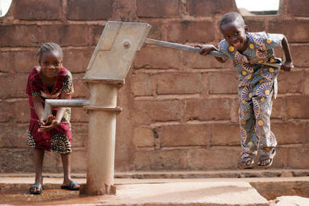 Happy Little African Boy Pumping Water For His Sister Stockfoto
