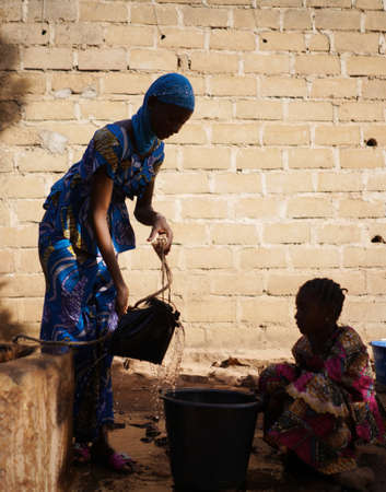Vertical Candid Photo of Malian African Girls Collecting Water