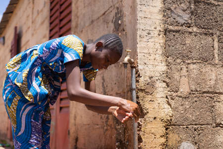African Woman Washing Hands under Tap Outdoors