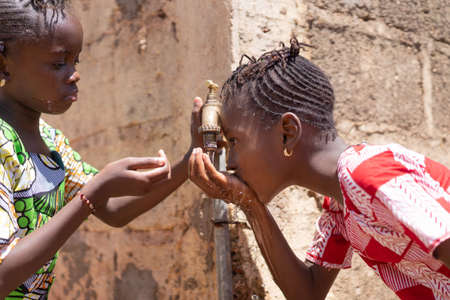 Togetherness symbol, Two Beautiful African Children Women Drinking Water Together