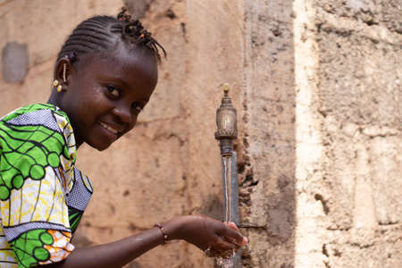 Little African Girl Happy in front of Water Tap Drinking