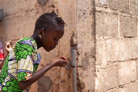 Candid Photograph of African Black Beautiful Girl drinking Freshwater