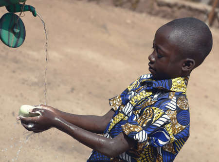 Outdoor Portrait of African Black Boy Washing Hands Outdoors to Fight Coronavirus Virus or Bacteria