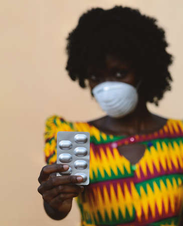 Virus Crisis around the world: African Woman Upper Body Shot with Mask and Medicament Pills