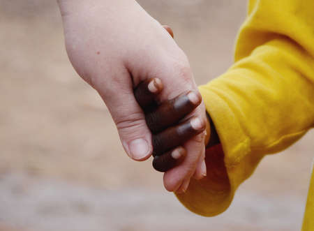 Close-up photo of African and Caucasian Hands Holding Together as a Human Rights symbol.