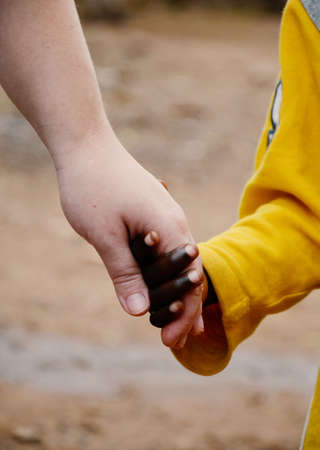 Close up shot of African child and caucasian woman holding hands peacefully and lovely together.
