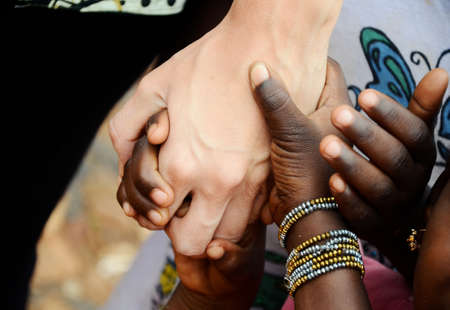 Togetherness symbol of African children and white caucasian woman holding hands outdoors.