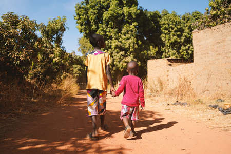 Two African Young Boys Walk Together in a Typical African Village