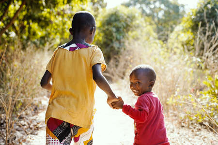 Smiling African Children Walking Outdoors in Typical Tribal Town Near Bamako, Mali (Africa)