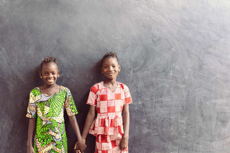 African Black Sisters Posing in Front of Blackboard as a School Education for Africa Symbol Zdjęcie Seryjne