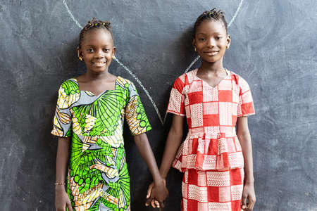 Couple of African Children Posing Indoors in School Building Holding Hands