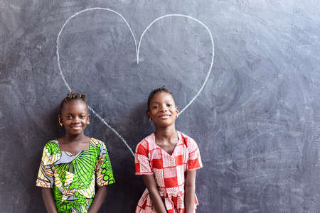 Two Nice Cute African Black Girls Standing in Front of Blackboard with Big Heart Love Symbol Archivio Fotografico