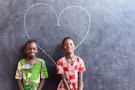 Two Nice Cute African Black Girls Standing in Front of Blackboard with Big Heart Love Symbol Zdjęcie Seryjne